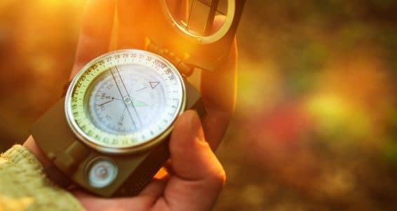 Hiking with Small Compass Device. Compass in a Hand.