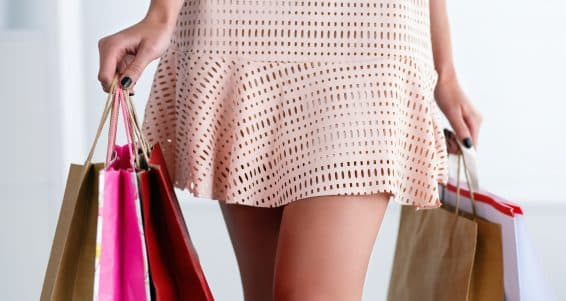 Beautiful walking legs of a woman in dress holding colored paper bags. Shopping consumerism and present or stylist concept. Shop and boutique visiting concept
