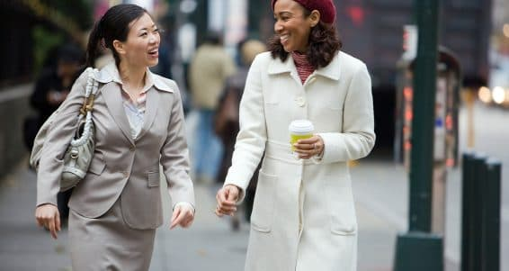 Two business women having a conversation while walking in the big city.