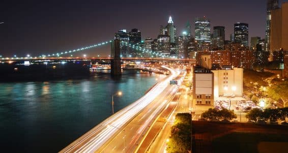 Urban New York City Manhattan skyline and Brooklyn Bridge with skyscrapers over Hudson River illuminated with lights and busy traffic at dusk after sunset.