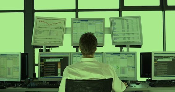 Rear view of stock trader looking at multiple computer screens