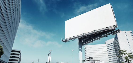 Big white blank billboard in modern city over blue sky background.