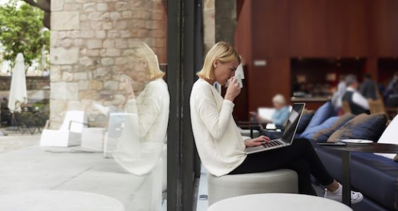 Confident business woman looking at laptop computer screen and enjoying her cup of coffee