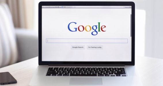 Macbook Pro Retina With Google Home Page On The Screen Stands On A White Table