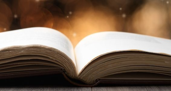 Open book on wooden table with bokeh effect in the background
