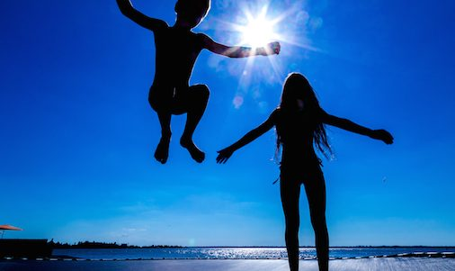 Two kids jumping on trampoline