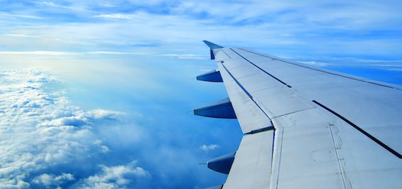 Wing of an airplane flying above the clouds. people looks at the sky from the window of the plane, u