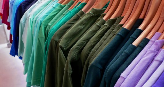 display of rainbow colored t-shirts on wooden hangers.