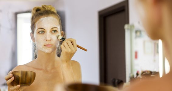 Young beautiful woman in a mask for the face of the therapeutic white mud. Spa treatment
