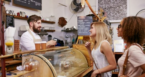 Shot of a young women friends placing an order in a coffee shop. Waiter taking coffee order from two young female costumers standing at cafe counter.