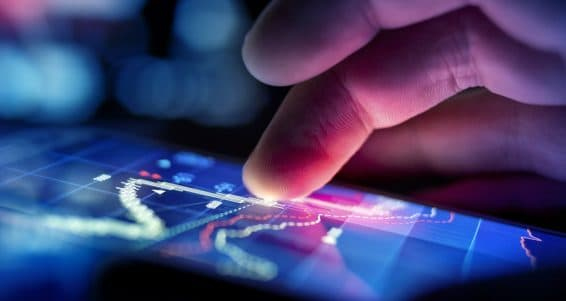 A city businessman using a mobile device to check stocks and market data. Close up shot.