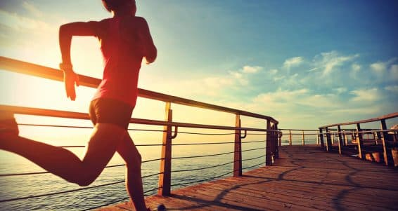 healthy lifestyle sports woman running on wooden boardwalk sunrise seaside ** Note: Soft Focus at 100%, best at smaller sizes