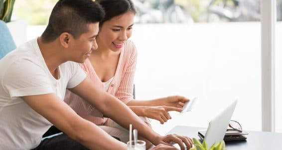 Couple entering information from the credit card to shop online