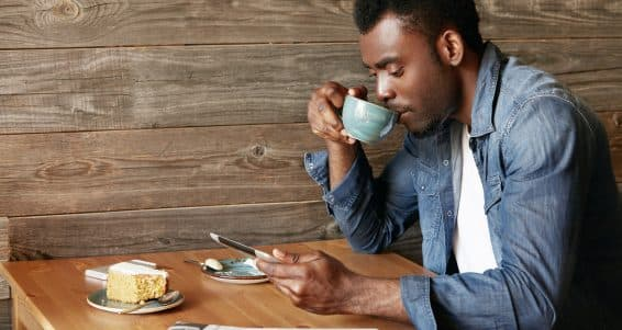 Handsome black male in casual wear checking email or reading world news on digital tablet computer drinking morning cappuccino sitting at the wooden table at a cozy cafe. Connection and technology