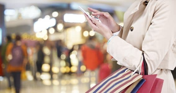 hands of a young woman using mobile phone in modern shopping mall.