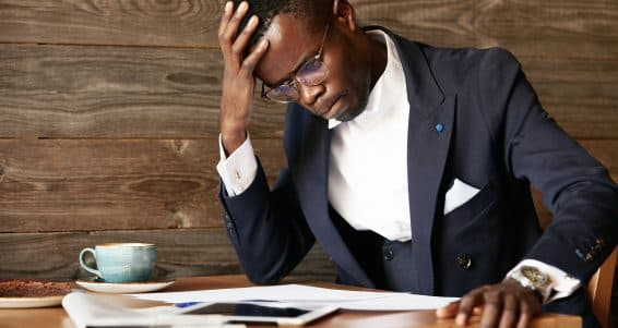 Young African businessman looking puzzled having a computer problem sitting in deep thinking pose touching his forehead squeezing lips and looking at papers resting his elbow on the table