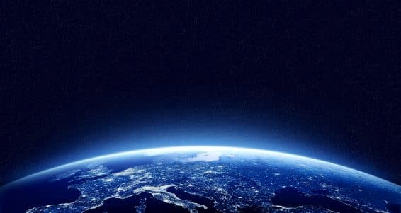 Earth at night as seen from space with blue glowing atmosphere and space at the top. Perfect for illustrations. Elements of this image furnished by NASA
