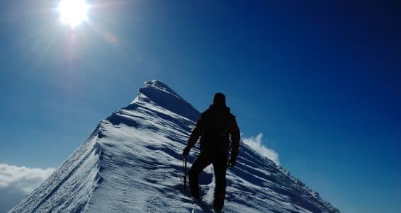 A lonely climber reaching the summit of the mountain