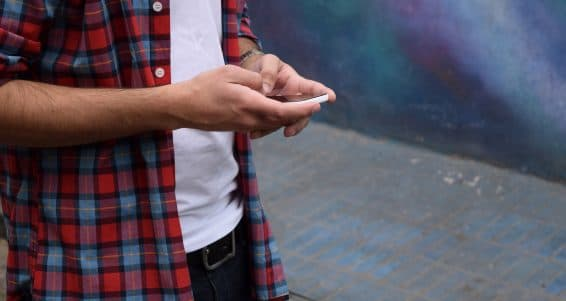 Casual young latin man using a smartphone.