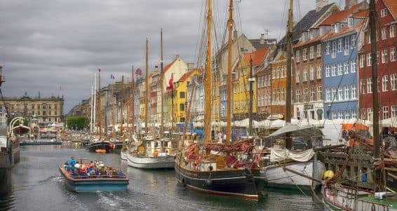 COPENHAGEN DENMARK - JUNE 8: Tour-boat people and sailboats in Nyhavn Canal in Copenhagen Denmark June 8 2016