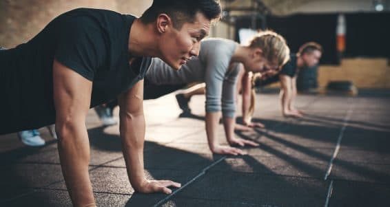 Fit young people doing pushups in a gym looking focused
