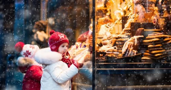 Children window shopping on traditional Christmas market in Germany on snowy winter day. Kids buying candy pastry and gingerbread in confectionery. Boy and girl choosing sweets in Xmas bakery.