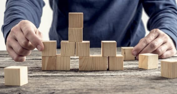 Man in blue shirt arranging wooden blocks on rustic table in a conceptual image.