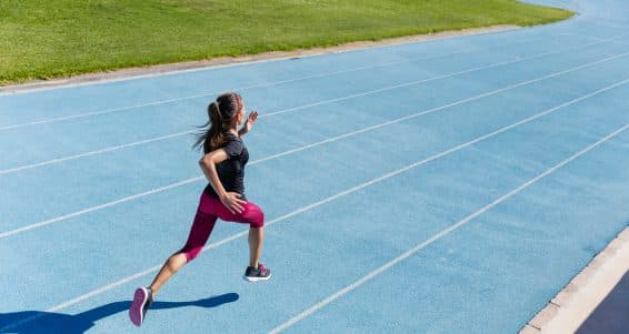 Runner sprinting towards success on run path running athletic track. Goal achievement concept. Female athlete sprinter doing a fast sprint for competition on blue lane at an outdoor field stadium.