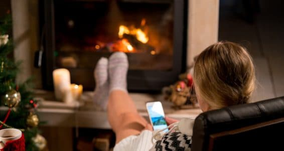 Woman is resting with phone near the fireplace