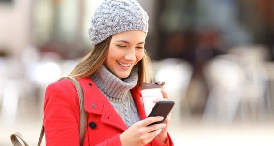 Happy fashion woman using a smart phone and holding a take away coffee in the street in winter