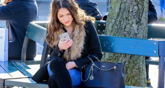 Lund Sweden - March 12 2016: Young and attractive adult female texting on Apple Iphone while smiling. Backlit with sunlight in her hair. Real people in everyday life.