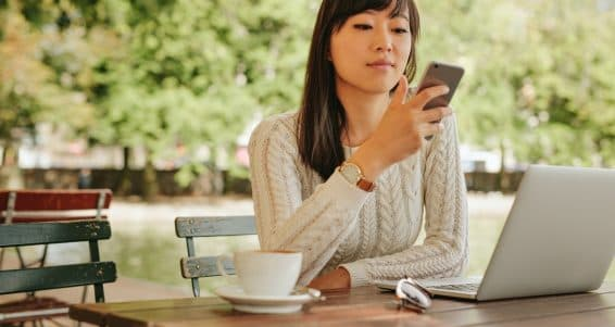 Shot of attractive asian woman using smartphone at outdoor coffee shop. Female sitting at cafe table outdoors using mobile phone.