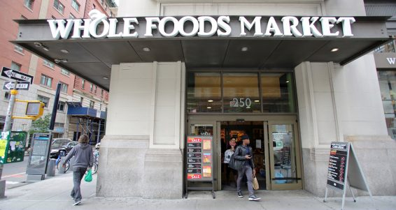 NEW YORK CITY - OCT 23 2013: Shoppers enter a Whole Foods Market supermarket in Manhattan on Wednesday, October 23, 2013. Whole Foods Market, Inc. is an American foods supermarket chain