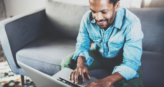 Attractive bearded African man spending free time in sofa, writing email on laptop at modern home.Concept of young people enjoying mobile devices.Blurred background.