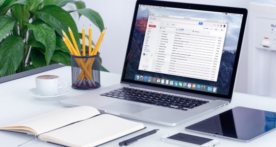 Varna Bulgaria - May 29 2015: Google Gmail email inbox interface on the Apple MacBook Pro screen that is on office desk. Gmail is a free email service provided by Google. All gadgets in focus.