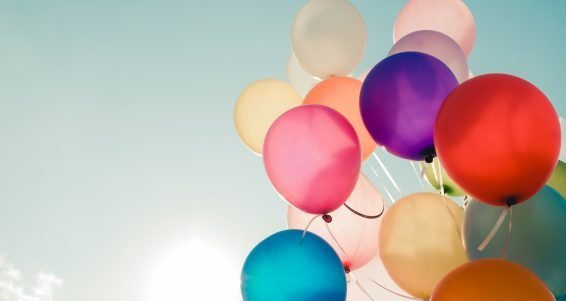 Colorful balloons flying on sky with a retro vintage filter effect. The concept of happy birthday in summer and wedding honeymoon party - usage for background (vintage color tone)