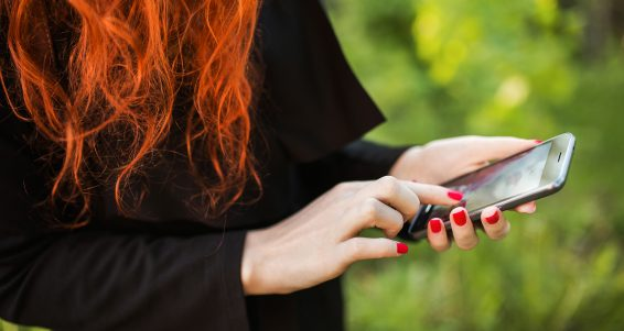 Red-haired stylish girl with a mobile phone on a background of green foliage. Retouch photo on mobile phone. Mobile gadget. Dial the number on your mobile phone. Modern mobile Internet. Hold in hand a mobile phone.