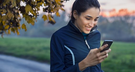 Young athlete looking at phone and smiling at park during sunset. Smiling young woman checking her smartphone while resting. Happy girl texting a phone message with a big smile on her face.