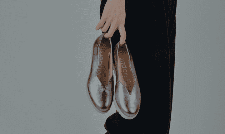 woman holding pair of silver flats