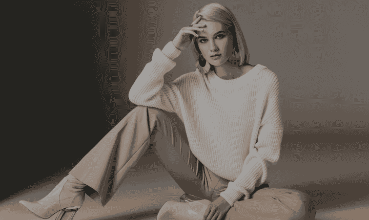seated fashion model wearing white sweater and boots