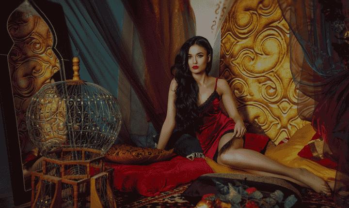 model seated before jewel toned fabrics