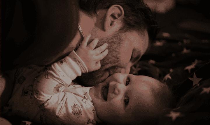 man kissing smiling baby