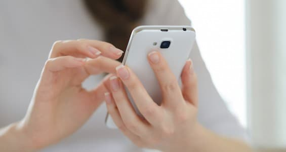 Woman Using Her Mobile Smart Phone at Home. Close-up of Mobile Phone